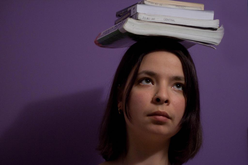 Woman balancing books on her head
