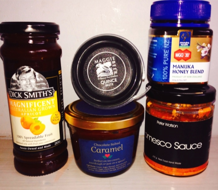 Photograph of assorted jars of condiments. From left to right: Dick Smith's Apricot, Maggie Beer's Quince Paste, Manuka Honey Blend and Peter Watson's Romesco Sauce.