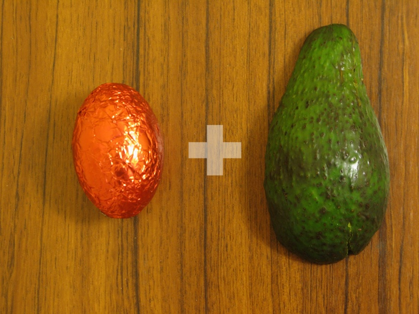 Photograph of an easter egg in orange foil and an avocado