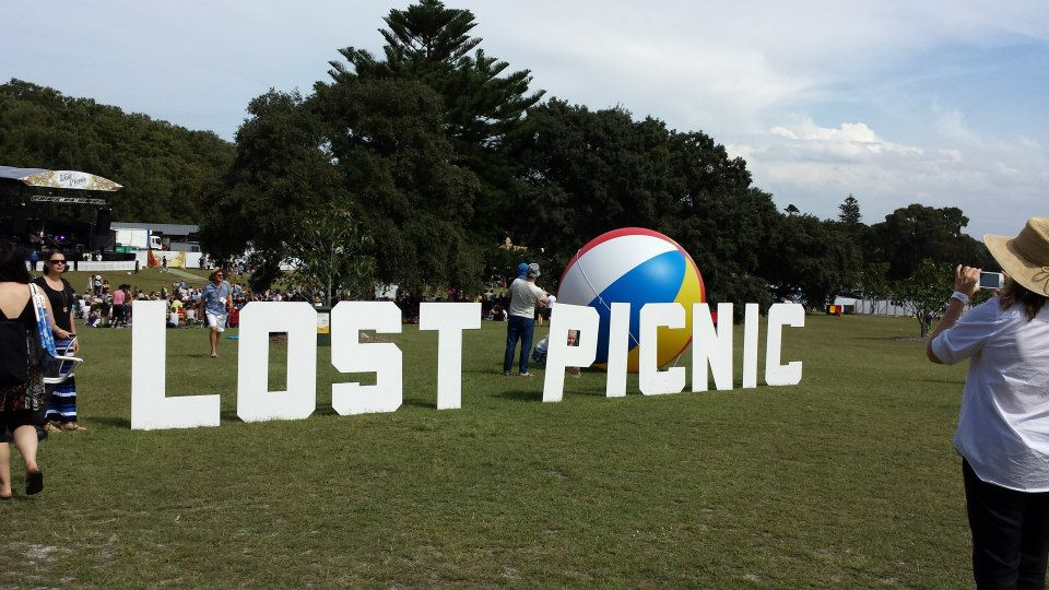 The Hollywood style sign for the Lost Picnic music festival. A large beach ball is in the background.