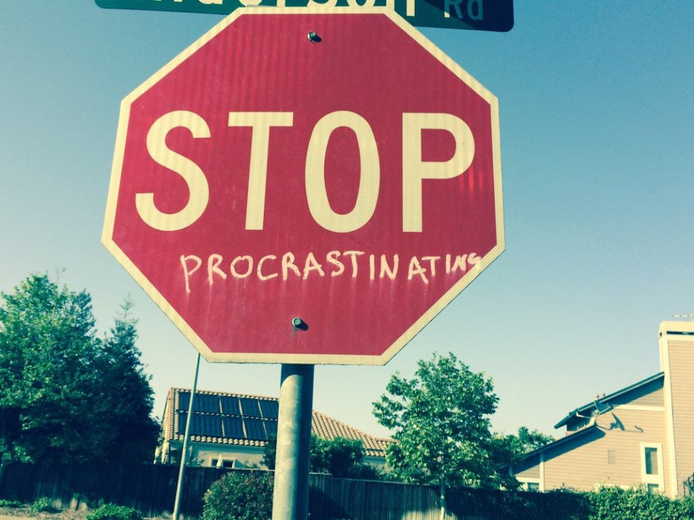 Stop sign graffitied to read 'Stop Procrastinating'