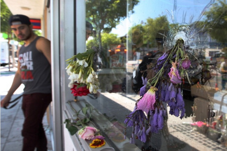 Flowers fill bullet holes from the May 25 shooting in the Californian community of Isla Vista.